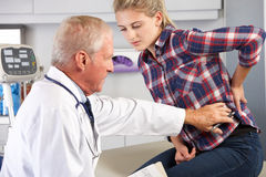 Teenage Girl Visits Doctor's Office With Back Pain Royalty Free Stock Photos