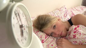 Teenage Girl Waking Up In Bed And Turning Off Alarm Clock. Teenage girl woken by alarm clock which she turns off before pulling duvet over her head.Shot on Sony stock footage