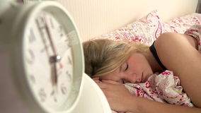 Teenage Girl Waking Up In Bed And Turning Off Alarm Clock. Teenage girl woken by alarm clock which she turns off before pulling duvet over her head.Shot on Sony stock video