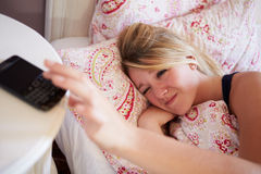 Teenage Girl Waking Up In Bed And Turning Off Alarm On Phone Royalty Free Stock Photography