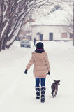 Teenage girl walking her dog in winter Royalty Free Stock Image