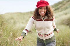 Teenage Girl Walking Through Sand Dunes. Wearing Warm Clothing Royalty Free Stock Photography