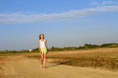 Teenage girl walking on the sandy road Royalty Free Stock Photo