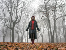 Teenage girl walking in a very foggy park Stock Image