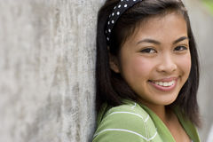 Teenage girl (13-15) by wall, smiling, portrait, close-up Royalty Free Stock Images