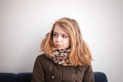 Teenage girl in warm outwear sitting on blue sofa Royalty Free Stock Image