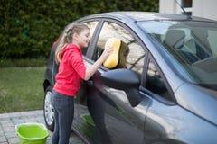 Teenage girl washing a car Stock Images