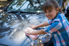 Teenage girl washing a car on a sunny day Royalty Free Stock Photography