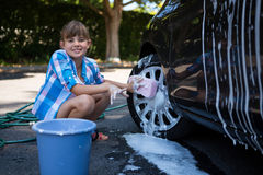 Teenage girl washing a car on a sunny day Royalty Free Stock Photos