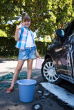 Teenage girl washing a car on a sunny day Stock Photography