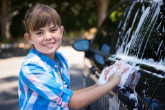 Teenage girl washing a car on a sunny day Stock Images