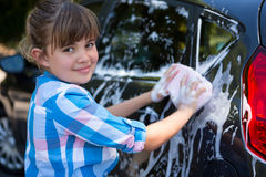 Teenage girl washing a car on a sunny day Royalty Free Stock Image
