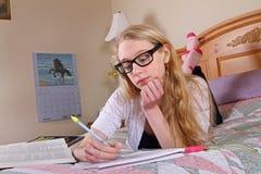 A teenage girl wearing glasses studies stock images