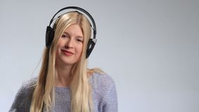 Teenage girl wearing headphones listens to music stock video
