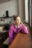 Teenage girl wearing pink sweatshirt looking into window stock image