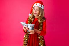 A teenage girl wearing a Santa hat and tinsel around her neck, h royalty free stock photo