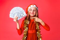 A teenage girl, wearing a Santa hat and with tinsel on her neck, with dollars in her hands, and points at them with her finger royalty free stock photo