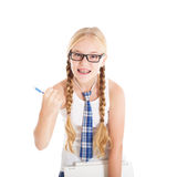 Teenage girl wearing a school uniform and glasses holding a laptop. Girl showing a fist. Stock Image