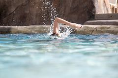 Girl swimming fast in pool stock image