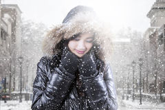 Teenage girl wearing winter jacket in the city. Photo of pretty teenage girl standing on the street while wearing winter jacket in snowfall day Royalty Free Stock Photography