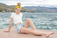 Teenage girl wearing yellow bandana at the lake stock photo