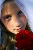 Teenage girl in wedding dress. Portrait of pretty young teenage girl wearing traditional white wedding dress and veil, holding bouquet of red flowers stock photos