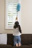 Teenage Girl Whisking At Window Stock Images