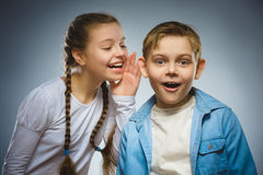 Teenage girl whispering in ear of boy on gray background. Communication concept. Teenage girl whispering in the ear of teen boys on a gray background. Positive Stock Photos