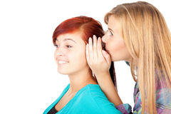 Teenage girl whispering in friend`s ear Royalty Free Stock Photo