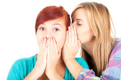 Teenage girl whispering in friend`s ear Royalty Free Stock Photography