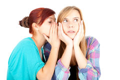 Teenage girl whispering in friend`s ear Stock Photo