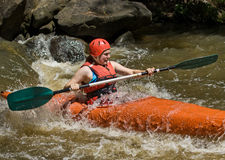 Teenage girl white water kayaking Stock Images
