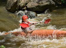 Teenage girl white water kayaking Stock Photography