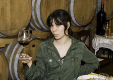 Teenage Girl at a Wine Tasting. An Amerasian teenage girl is holding a glass of red wine. She is at a wine tasting in San Gimignano, Italy. Wine barrels are in stock images