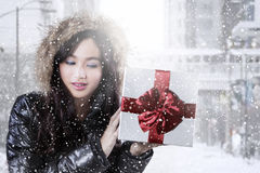 Teenage girl with winter clothes holding gift box Stock Photography