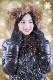 Teenage girl in winter clothes over lights background. Portrait of beautiful asian teenage girl wearing winter jacket with defocused lights background Royalty Free Stock Image