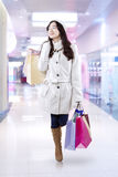 Teenage girl in winter coat walking at the mall Stock Photos