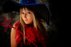 Teenage girl with wizard hat and magical wand. Teenage girl wearing wizard costume, studio shot Stock Photo