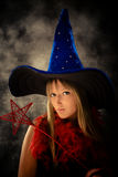 Teenage girl with wizard hat and wand. Blond teenage girl with wizard hat and wand, studio shot Royalty Free Stock Photos