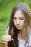 Teenage girl wonders on flower. Selective focus Royalty Free Stock Image