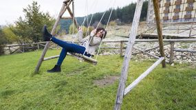 teenage girl on a wooden swing stock photography