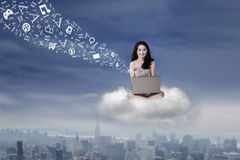 Teenage girl working with laptop on cloud Royalty Free Stock Photo