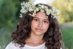 Teenage girl with a wreath of daisies on the Stock Image