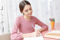 Teenage girl writing in her exercise book royalty free stock image