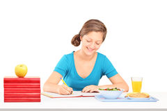 Teenage girl writing homework and having a meal Stock Photo