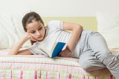 Teenage girl 10 years old in home clothes reads a book on the bed in her room Royalty Free Stock Photography