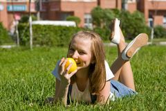 Teenage girl with a yellow apple Royalty Free Stock Photo