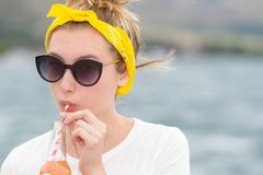 Teenage girl with yellow bandana and sunglasses drinking from a stock photography