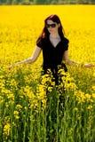 Teenage girl on yellow field. In spring Stock Photos