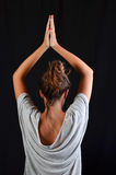 Teenage girl in Yoga pose. Teenage girl doing exercise in yoga pose, studio shot against black background Stock Photos